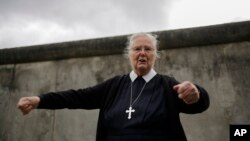 In this Sept. 18, 2019, photo, Sister Brigitte Queisser of the Lutheran Lazarus Order talks in front of concrete remains of the Berlin Wall during an interview with The Associated Press in Berlin