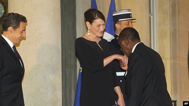 France's President Nicolas Sarkozy, left, and Carla Bruni-Sarkozy welcome Ivory Coast President Alassane Ouattara as he arrives for a state dinner at the Elysee Palace in Paris, January 26, 2012.