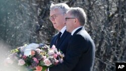CEOs of Germanwings Thomas Winkelmann, and Lufthansa Carsten Spohr (R) carry flowers at the memorial for the victims of the Germanwings jet crash, in Le Vernet, France, April 1, 2015.