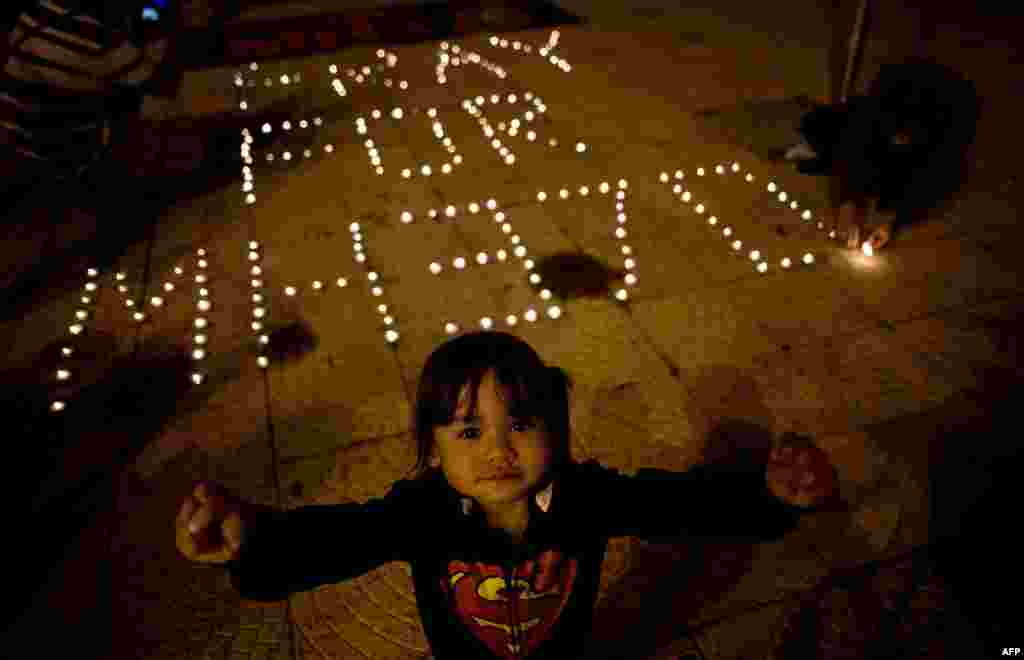 A child reacts to the camera as others light candles during a vigil for missing Malaysia Airlines passengers at the Independence Square in Kuala Lumpur, March 10, 2014.