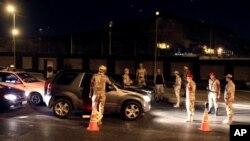 Fuerzas egipcias revisan vehículos en un retén en Nasr, Cairo. La capital continúa con toque de queda debido al estado de emergencia.
