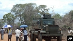 Internally displaced people walk past a military vehicle in the Zone 4 camp at Manik Farm in northern Sri Lanka, Aug. 19, 2009 (file photo)