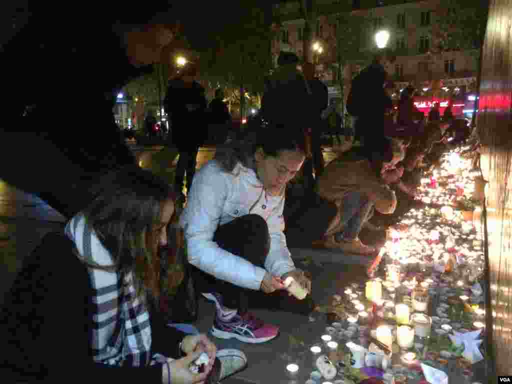 People pay homage to terror attack victims at the Place de la Republique square in Paris, France after panic spread about another possible attack, Nov. 15, 2015. (Photo: D. Schearf / VOA)