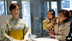 "Customers watch android robot ""Aiko Chihira"" at the reception of Mitsukoshi department store in Tokyo, Monday, April 20, 2015. The lifelike android robot, which was developed by Japanese electronics manufacturer Toshiba, marked her first day at work as a"