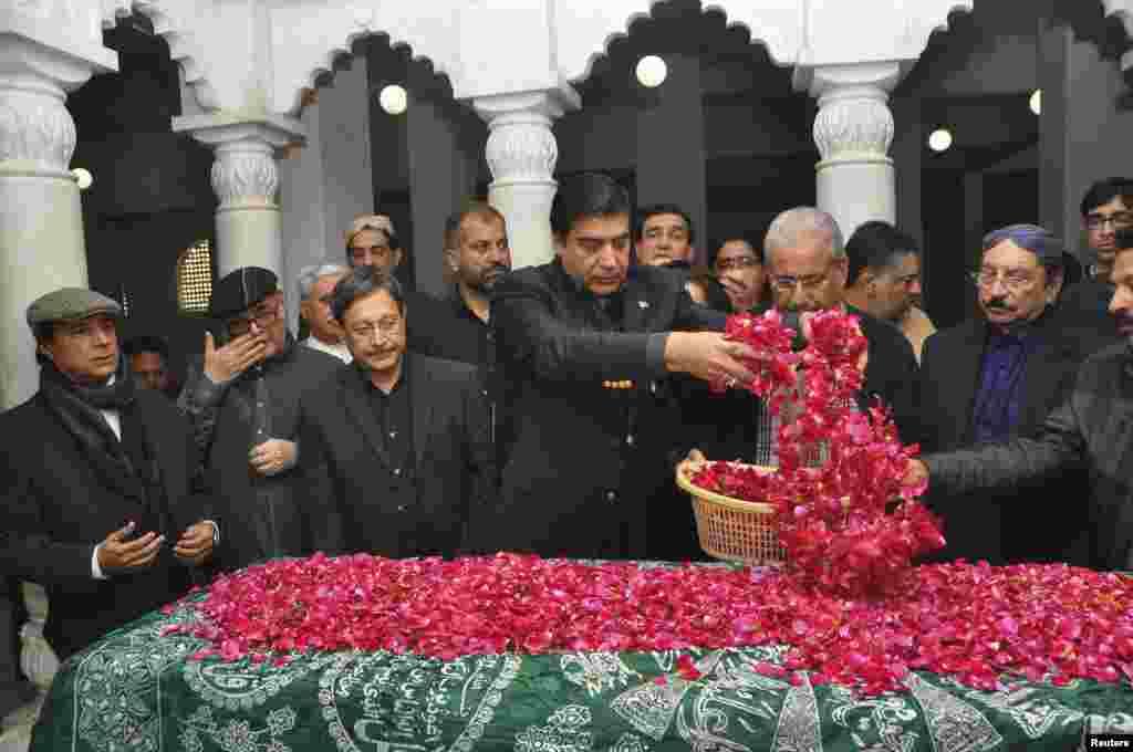 وزیر اعظم پرویز اشرف بے نظیر بھٹو کی قبر پر پھول نچھاور کر رہے ہیں