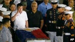 El presidente de Filipinas participa de una ceremonia ante el cuerpo del teniente de la Marina, John Frederick Savellano, uno de los doce marinos víctimas del enfrentamiento del viernes con militantes musulmanes.