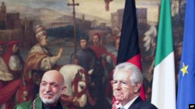 Italian Prime Minister Mario Monti (R) and Afghanistan's President Hamid Karzai shake hands after signing of documents during a meeting at the Chigi Palace in Rome January 26, 2012.