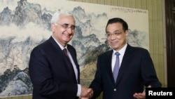 PM China Li Keqiang (kanan) berjabat tangan dengan Menlu India Salman Khurshid di Beijing (10/5).
