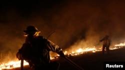 Seorang petugas berusaha memadamkan kobaran api yang melanda kawasan pegunungan Santa Monica, negara bagian California (5/5).