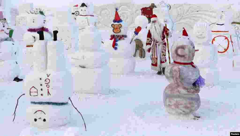 បុរសម្នាក់ស្លៀកពាក់ជា Ded Moroz (ឬលោកតា Frost) ក្នុងភាសារុស្ស៊ីដែលមានន័យថា Santa Claus ដើររើសមនុស្សព្រិលល្អបំផុត ក្នុងពិធីប្រកួតប្រជែងដែលមានឈ្មោះថា Parade of Snowmen នៅឧទ្យាន Royev Ruchey Flora and Fauna Park នៅជាយក្រុង Krasnoyarsk ប្រទេសរុស្ស៊ី។