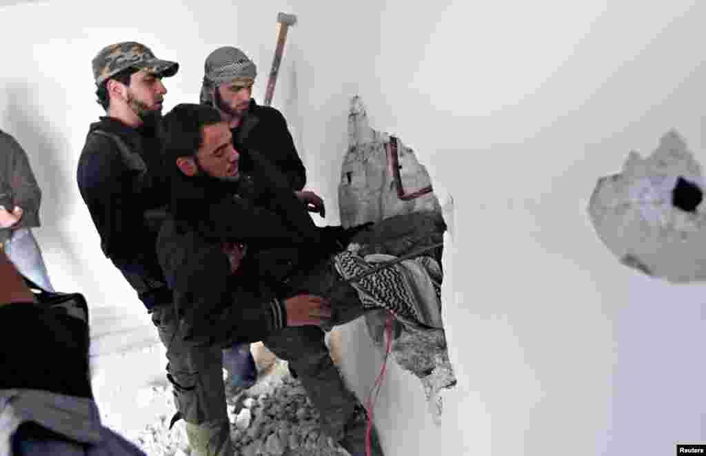 26일 다마스쿠스 교외 지역에 폭격이 있은 후, 부상자들 옮기는 반군 병사들.