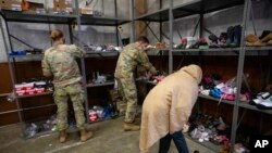 An Afghan refugee looks for donated shoes at the donation center at Fort McCoy U.S. Army base, Sept. 30, 2021, in Ft. McCoy, Wis.