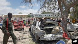 A Somali soldier walks near the wreckage of vehicles at the scene of a blast outside the compound of a district headquarters in the capital Mogadishu, Somalia Sunday, Sept. 2, 2018.