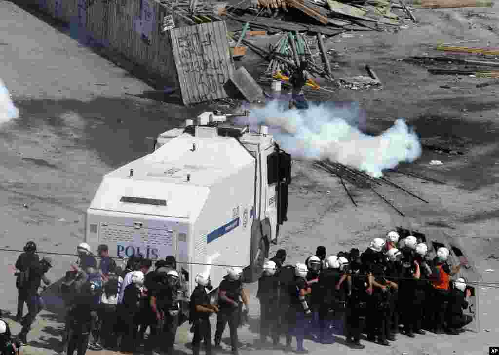 A protester runs to avoid tear gas as police take cover next to a water cannon in Taksim Square in Istanbul, June 11, 2013.