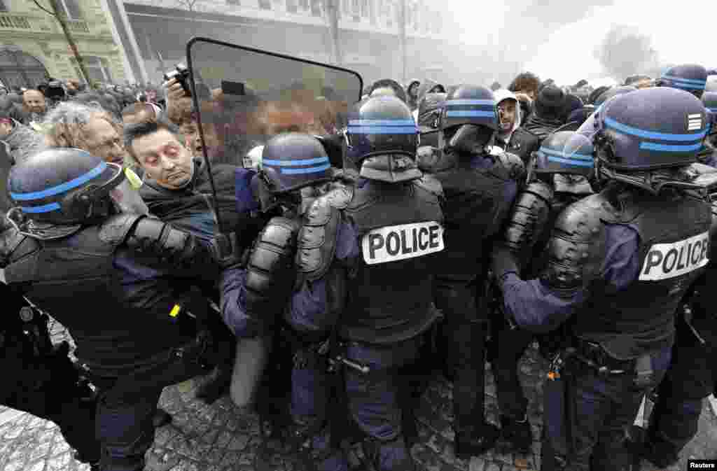 Employees of PSA Peugeot Citroen face French riot policemen during a demonstration in front of the Peugeot headquarters in Paris to protest the closure of the PSA Aulnay automobile plant, the government's economic policy, and industrial layoffs.