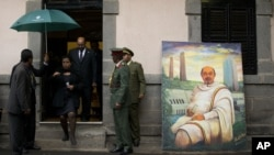 Sudan's President Omar al-Bashir, in doorway, walks past a portrait of late Ethiopian Prime Minister Meles Zenawi, a gift from another delegation, as he arrives to pay his respects to Meles' body lying in state at the national palace in Addis Ababa, Ethio