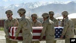 FILE - American soldiers carry the coffin of an American soldier in Afghanistan, April 26, 2003.