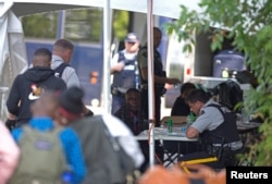 FILE - Refugees are processed by the Royal Canadian Mounted Police (RCMP) after crossing illegally into Canada at the U.S.-Canada border on Roxham Road from Champlain, New York, August 3, 2017.