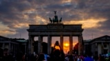Tourists take pictures as the sun sets behind the Brandenburg Gate in Berlin, Germany, Sept. 25, 2021.