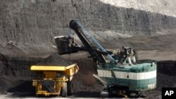 FILE - A mechanized shovel loads a haul truck with coal at the Spring Creek coal mine near Decker, Mont., April 4, 2013. A federal judge in Montana says the Trump administration failed to consider the environmental effects of resuming coal sales from fede