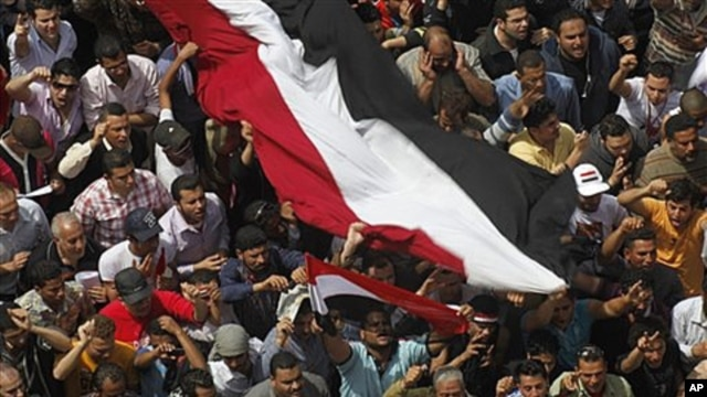 Egyptians shout as they wave a giant flag during a demonstration at Tahrir Square, Cairo, April 1, 2011