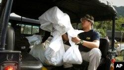Salah seorang anggota tim forensik Malaysia membawa tas-tas berisi jenazah yang ditemukan di perkemahan yang ditinggalkan di wilayah Wang Kelian, perbatasan Malaysia-Thailand, Senin (25/5).