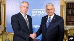 PM Turki Binali Yildirim (kanan) berjabat tangan dengan Menhan AS James Mattis dalam pertemuan di London, Kamis (11/5).