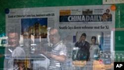 北京民眾走過一處陳列著《中國日報》的報攤(美聯社2015年9月23日)