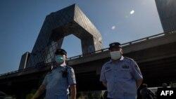 两名警察在北京街头巡逻,背景是中国中央电视台大楼。(2020年5月19日)