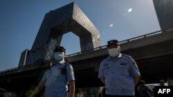 兩名警察在北京街頭巡邏,背景是中國中央電視台大樓。(2020年5月19日)