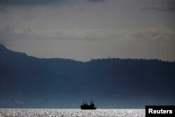 FILE - A fishing trawler anchors off the coast of Freetown, Sierra Leone, Nov.18, 2012.