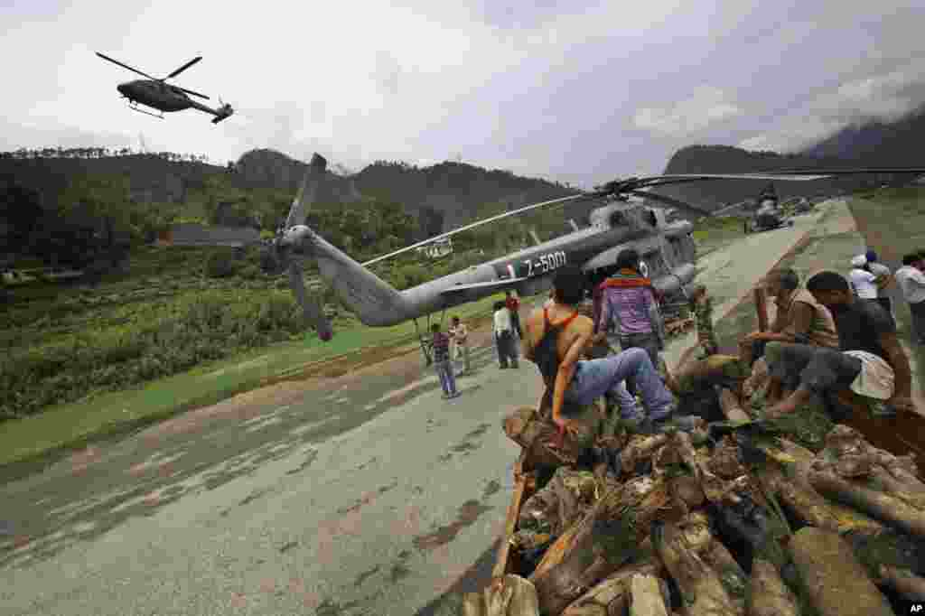 Locals unload wood from a truck to be loaded on to Indian Air force helicopters, in Gauchar, Uttarakhand, India, June 25, 2013.