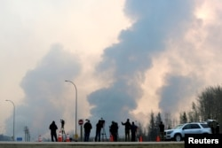 Journalists look on as smoke rises from wildfires south of Fort McMurray, Alberta, Canada, May 6, 2016.