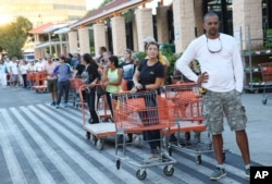 Eduardo Soriano of Miami waits in a line since dawn to purchase plywood sheets at a Home Depot store in North Miami, Florida, Sept. 6, 2017.