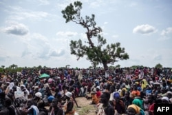FILE - Thousands of people wait in the hot sun near the air drop zone in Leer, South Sudan, July 5, 2014.