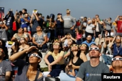 People watch the solar eclipse on the lawn of Griffith Observatory in Los Angeles, California, U.S., August 21, 2017.