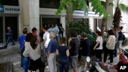 People stand in a queue to use ATMs of a bank in central Athens, Sunday, June 28, 2015.