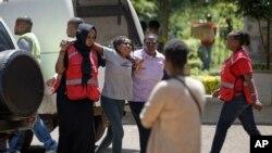 Ndugu wa mmoja wa wale walioathiriwa na shambulizi la kigaidi akisindikizwa na wafanyakazi wa Msalaba Mwekundu akiwa na majonzi baada ya kwenda kwenye chumba cha kuhifadhi maiti jijini Nairobi, Kenya Alhamisi, Jan. 17, 2019.