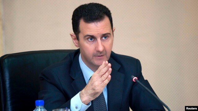 FILE - Syria's President Bashar al-Assad heads a cabinet meeting in Damascus, in this handout photograph distributed by Syria's national news agency SANA, Feb. 12, 2013.