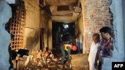 Petugas penyelamat Pakistan mengumpulkan barang bukti kebakaran pada sebuah pabrik sepatu di Lahore yang menewaskan sedikitnya 25 orang (12/9).