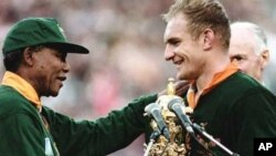 FILE - Nelson Mandela, himself wearing a Springbok rugby jersey, presents the World Cup trophy to South Africa team captain, Francois Pienaar, at Johannesburg's Ellis Park Stadium in 1995.