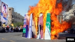 آتش زدن پرچم عربستان سعودی در کنار پرچم های آمریکا و اسرائیل در راهپیمایی روز قدس در ایران - ۲۶ تیر ۱۳۹۴