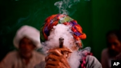 An Indian villager smokes tobacco in New Delhi, India, 2013. A World Health Organization study says tobacco-related diseases cost India about $22 billion in 2011.