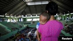 Seorang perempuan menggendong anaknya di sebuah aula olahraga di daerah Klungkung, Bali, yang menjadi pusat evakuasi sementara bagi warga yang tinggal di dekat Gunung Agung, 28 September 2017. (REUTERS/Darren Whiteside).