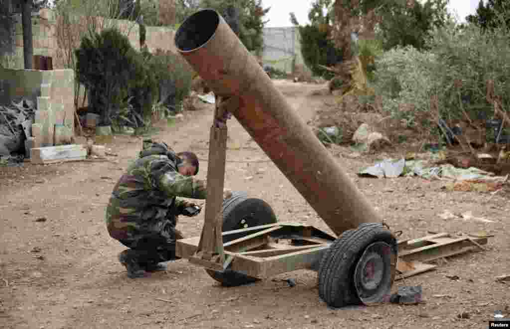 A Syrian Army soldier loyal to Syrian President Bashar al-Assad inspects a mortar used by Free Syrian Army fighters, in Ard al-Hamra, Aleppo, Feb. 27, 2014.