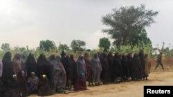 Un homme portant le drapeau de Boko Haram passe devant un groupe de 82 filles Chibok tenues en captivité pendant trois ans par des militants islamistes en attente d'être libérés en échange de plusieurs commandants militants, près de Kumshe, Nigeria, 6 mai 2017 .