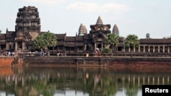 Tourists walk along the outer wall of Angkor Wat, reflected in its moat in Siem Reap, December 9, 2007.