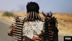 Un combatiente de la oposición cargando municiones mientras avanzan hacia la oriental ciudad de Sirte.