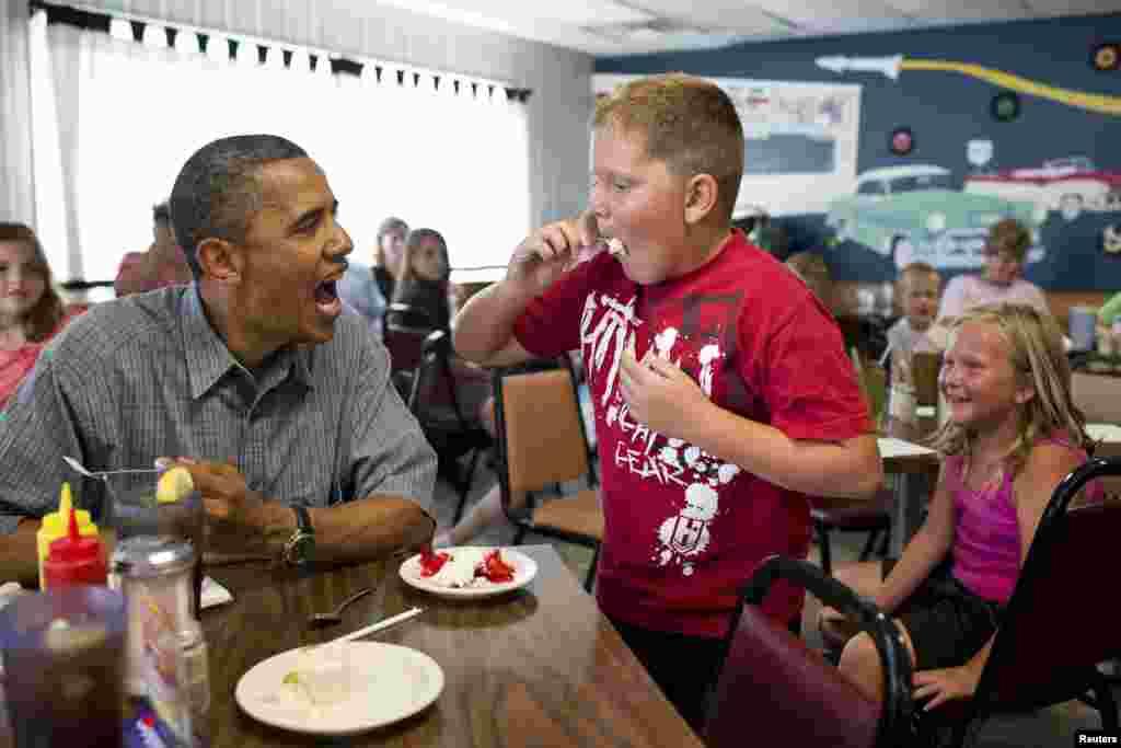 El presidente Barack Obama comparte su pastel de fresas con un muchacho en Oak Harbor, Ohio.