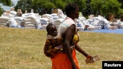 A Zimbabwean collects her monthly rations of food aid from Rutaura Primary School in the Rushinga district of Mount Darwin, north of Harare, March 7, 2013.